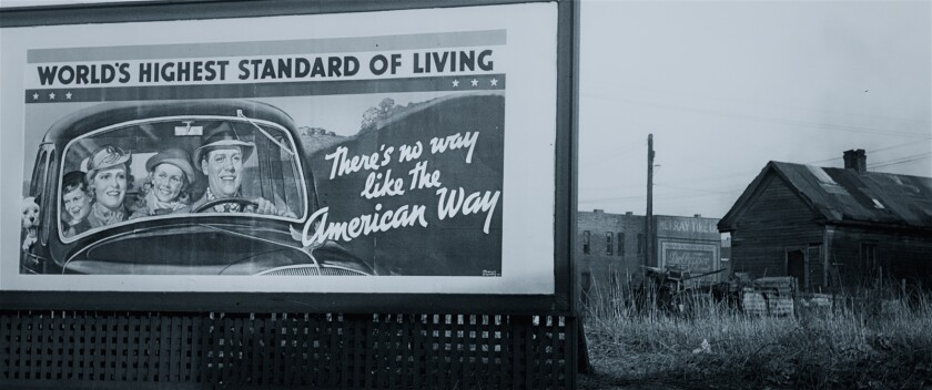 A billboard reads 'World's highest standard of living: There's no way like the American way,' from the documentary 'Capital in the Twenty-First Century'