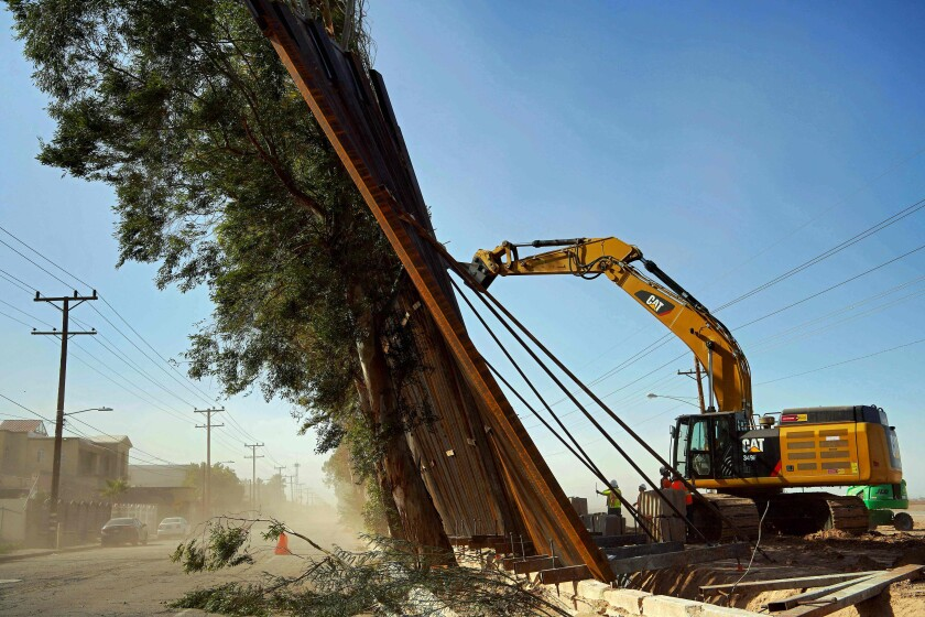 A construction crew works on a fallen section of the border wall as seen from Mexicali, Mexico, on Wednesday. Newly installed panels in Calexico, Calif., fell over in high winds, landing on trees on the Mexican side of the border.