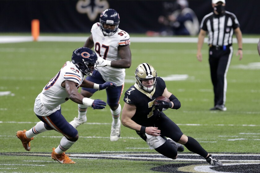 New Orleans Saints quarterback Taysom Hill (7) is pursued by Chicago Bears outside linebacker Barkevious Mingo (50) after catching a pass in the second half of an NFL wild-card playoff football game in New Orleans, Sunday, Jan. 10, 2021. (AP Photo/Brett Duke)