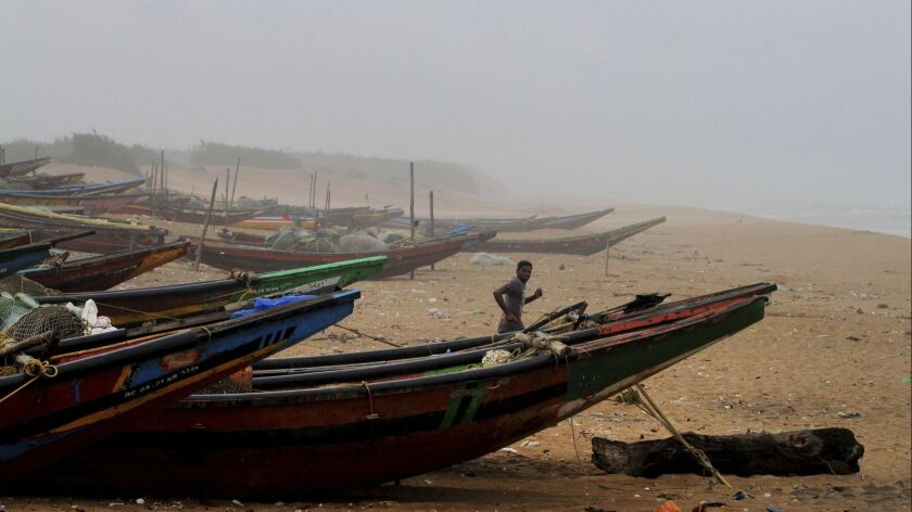 An Indian fisherman runs between the docked fishing boats amid strong winds at Chandrabhaga beach in
