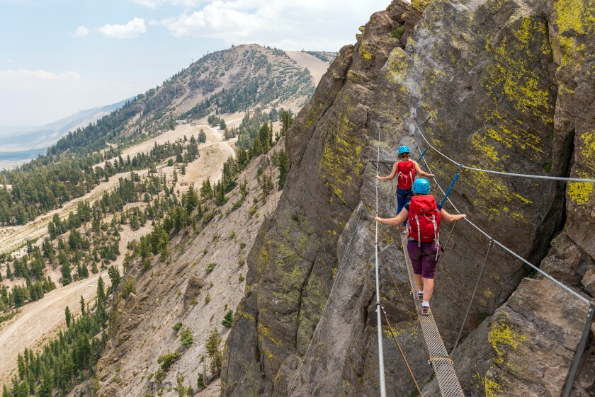 People walk on a narrow suspended plank with handholds at Mammoth Mountain's Adventure Center.