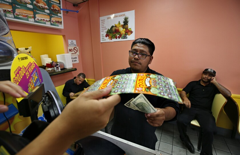Mike Luna, a waiter at Frida, a Mexican restaurant in the Americana at Brand shopping center in Glendale, buys a scratchers lottery ticket at Christina Donuts.