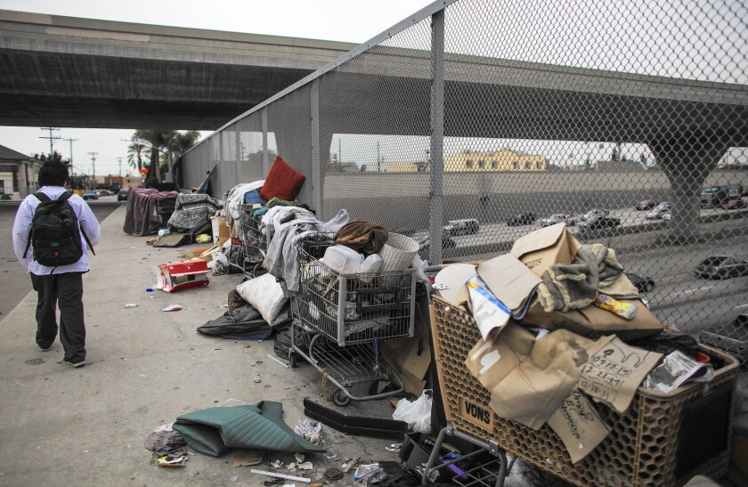 """Trash in piles and in shopping carts sit on a sidewalk under the 110 Freeway at 42nd Street. """"There's something systemic that has occurred in the city that didn't happen overnight,"""" City Administrator Miguel Santana said."""