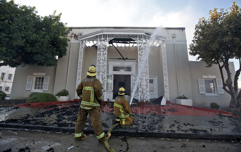 Los Angeles County firefighters hose down the still-smoldering Good Shepherd Bible Church in Whittier.
