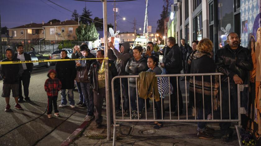 Vecinos, familiares y amistades de las víctimas se reúnen a un lado del almacén que se incendió en Oakland, arrebatándole la vida, hasta el momento a 30 personas. David Butow / Redux / For the Times
