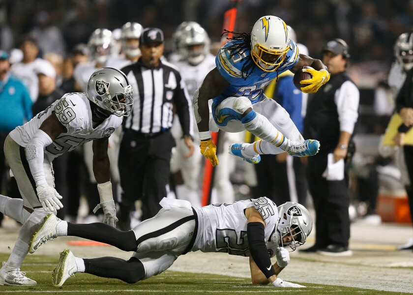 Chargers running back Melvin Gordon jumps over Oakland Raiders safety Erik Harris.