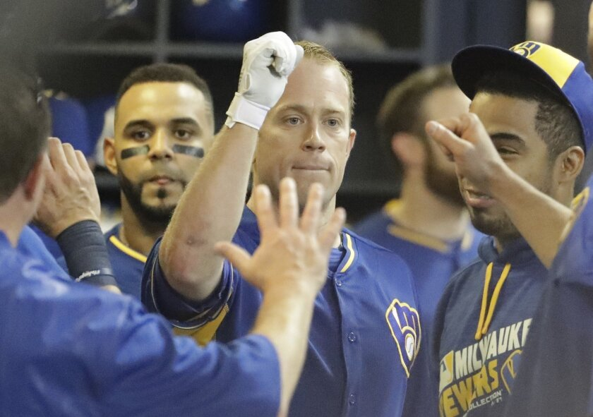 Milwaukee Brewers' Aaron Hill is congratulated after hitting a home run during the fifth inning of a baseball game against the Cincinnati Reds Friday, May 27, 2016, in Milwaukee. (AP Photo/Morry Gash)