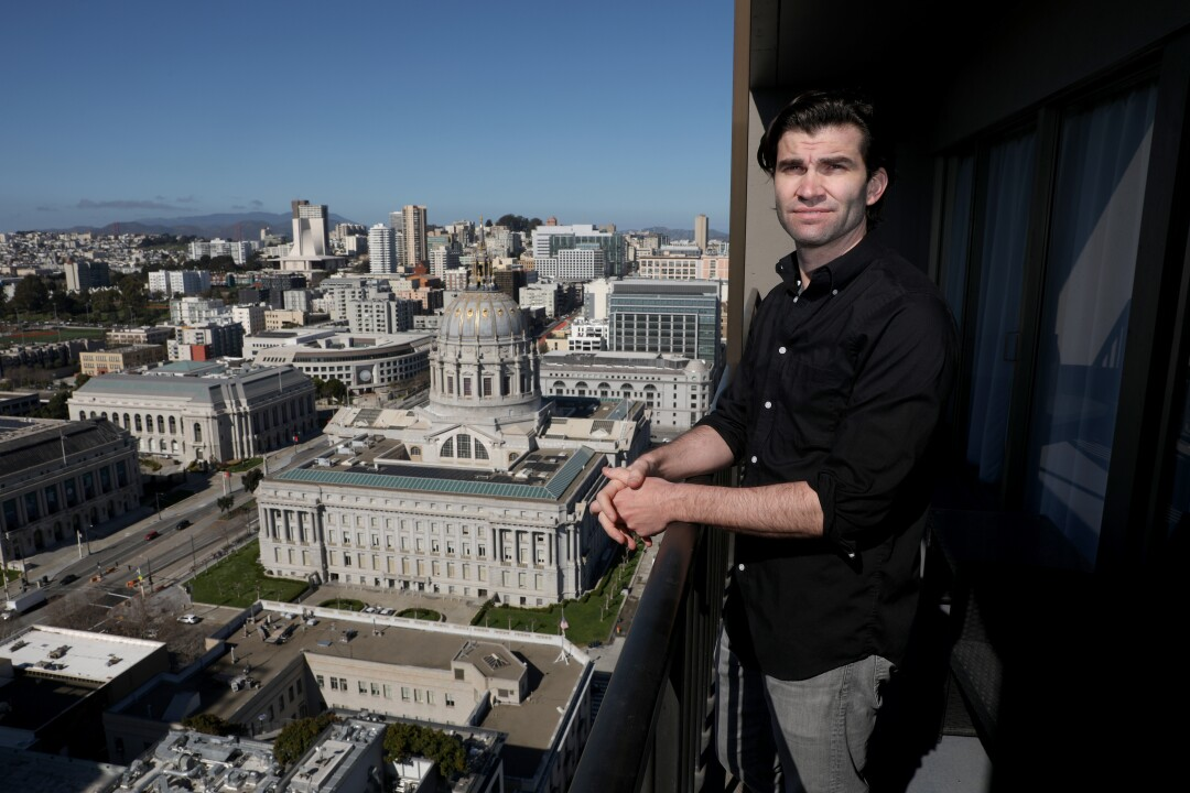 Scott Simmons at his one bedroom apartment balcony overlooking City Hall and other buildings in San Francisco