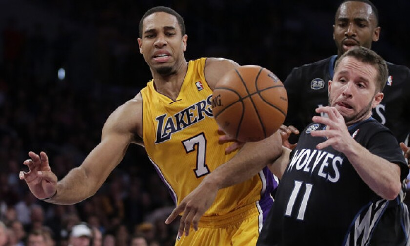 Lakers forward Xavier Henry (7) battles Minnesota Timberwolves guard J.J. Barea for a loose ball during a game in December.