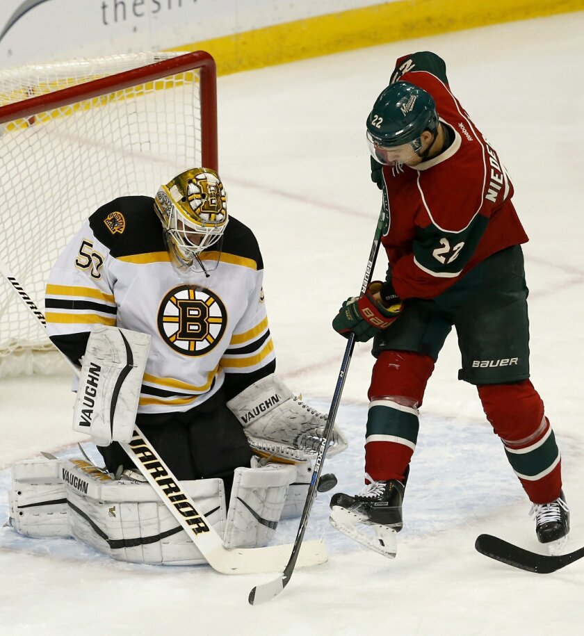 Boston Bruins goalie Jonas Gustavsson (50), of Sweden, deflects a shot by Minnesota Wild right wing Nino Niederreiter (22), of Switzerland, during the first period of an NHL hockey game in St. Paul, Minn., Saturday, Feb. 13, 2016. (AP Photo/Ann Heisenfelt)