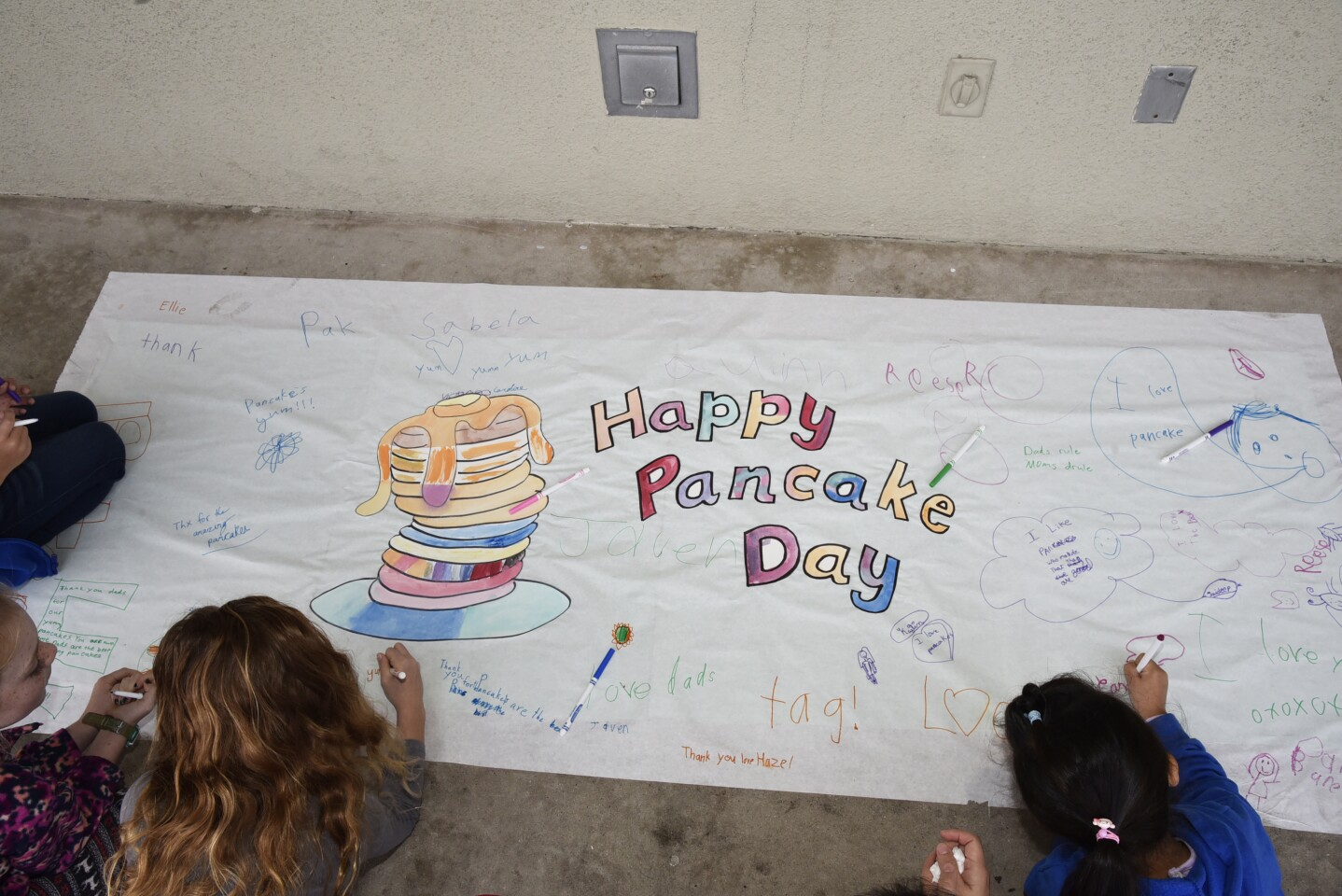 Students sign the Pancake Day poster