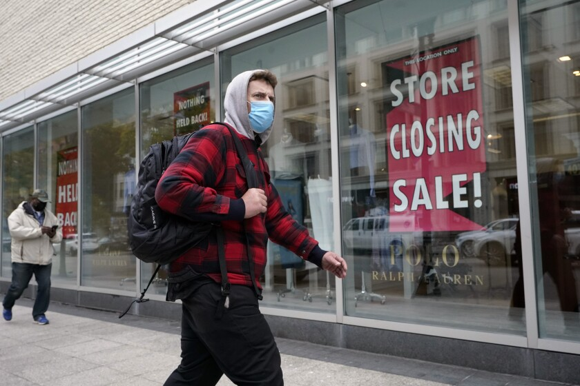 "A man walks past a sign in a store window that says: ""store closing sale"""