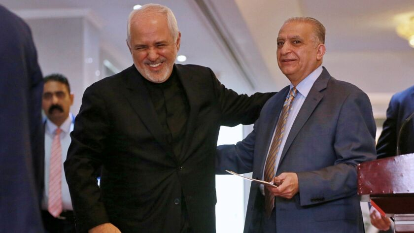 Iraqi Foreign Minister Mohammed Hakim, right, talks with his Iranian counterpart Mohammad Javad Zarif, after their news conference at the Ministry of Foreign Affairs in Baghdad on Sunday.