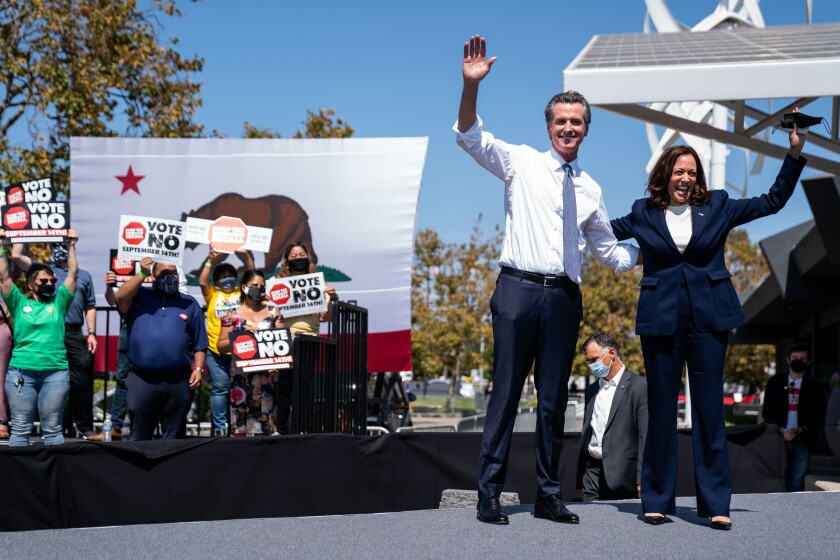 """Gavin Newsom and Kamala Harris wave onstage as supporters hold """"Vote no"""" signs"""
