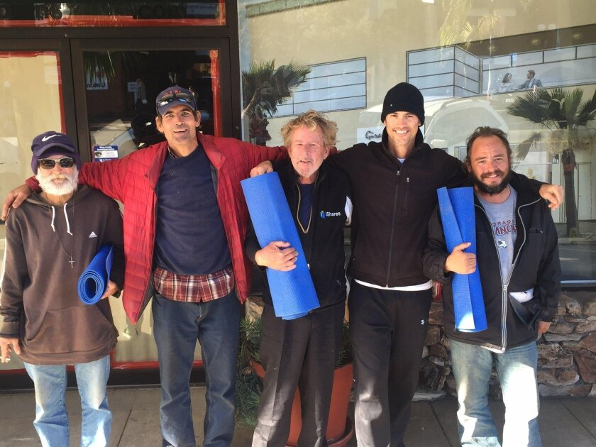 Andrew Beinbrink, second from right, founded Yoga 4 Homeless. He is shown from a few months ago giving yoga mats for some homeless men, including Mark Heffron, second from left.