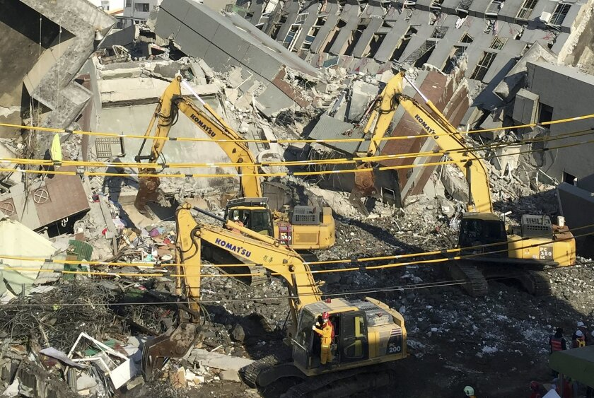 Rescue workers using excavators continue to search the rubble of a collapsed building complex in Tainan, Taiwan, Tuesday, Feb. 9, 2016. At least four people, including an 8-year-old girl, were rescued Monday from a high-rise Taiwanese apartment building toppled by a powerful quake two days earlier,