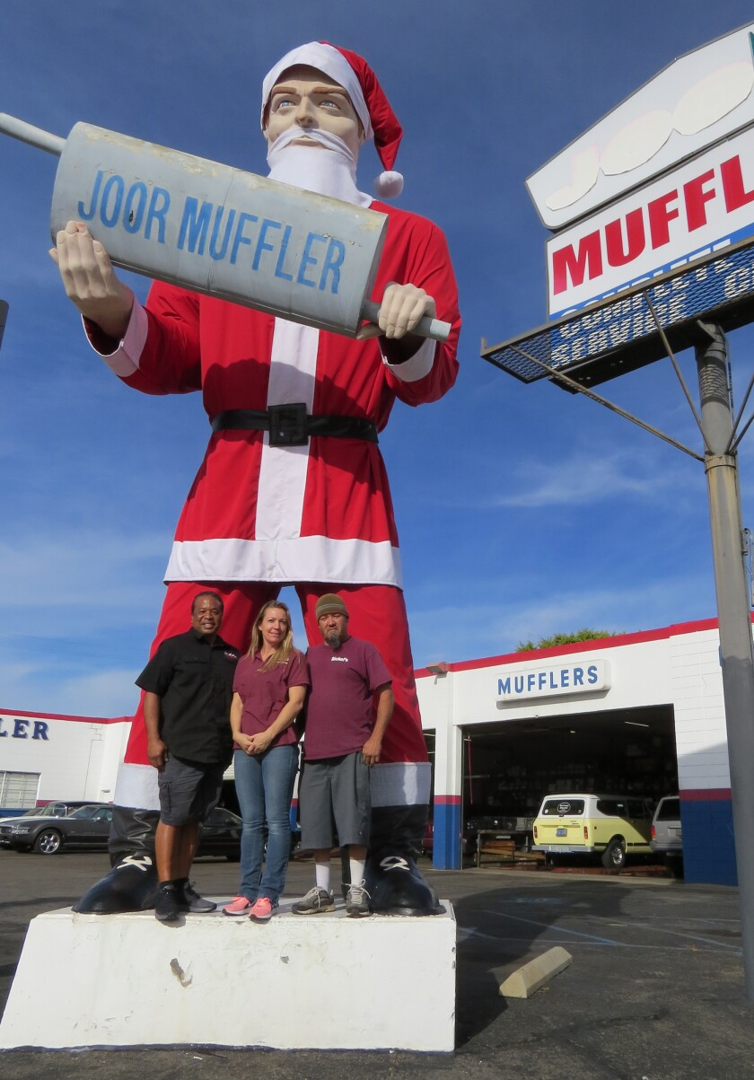 Nick Manning, owner of Joor Muffler & Auto Service, left, with Sickel's Fabrics & Upholstery store co-owners Michelle Guillen and Felix Guillen, pose with the newly costumed Joor Muffler Man in Escondido on Thursday, Dec. 5.