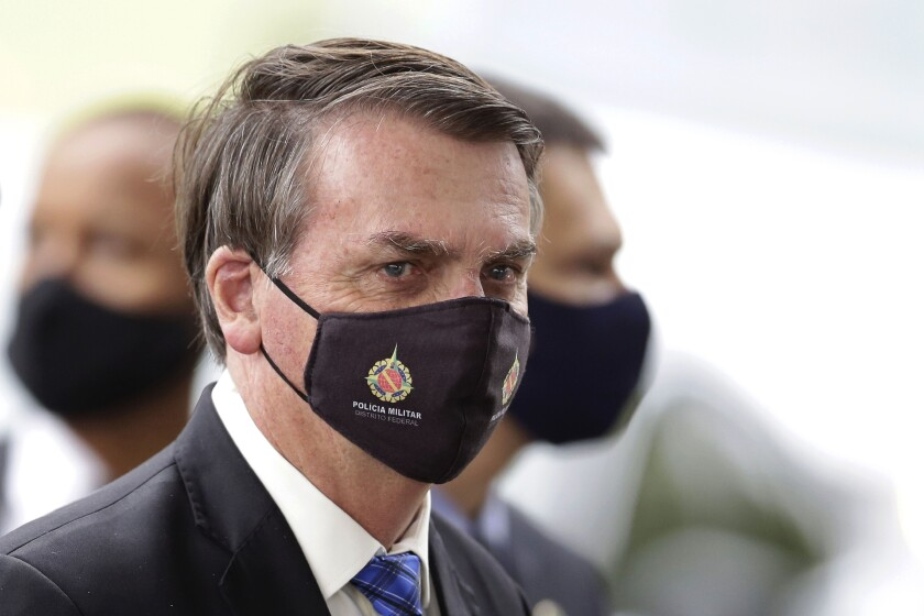 "FILE - In this May 18, 2020, file photo, Brazilian President Jair Bolsonaro wears a mask due to the coronavirus pandemic as he talks with supporters upon departure from his official residence, Alvorada palace, in Brasilia, Brazil. The logo on the mask reads ""Military Police. Federal District."" After 35 years of civilian-led democracy, Bolsonaro has created the most militarized Brazilian government since the fall of the country's army-led dictatorship. (AP Photo/Eraldo Peres, File)"