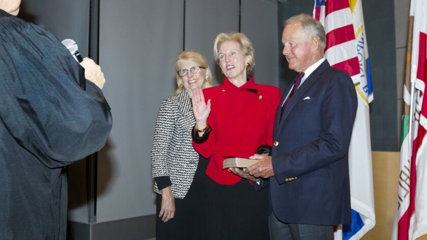 Diane Dixon, center, take the oath of office for Mayor as she stands with family members during a sw