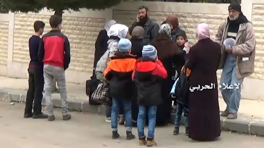 Syrian families gather to leave in buses from Madaya, an opposition-held town near Damascus, on Friday.