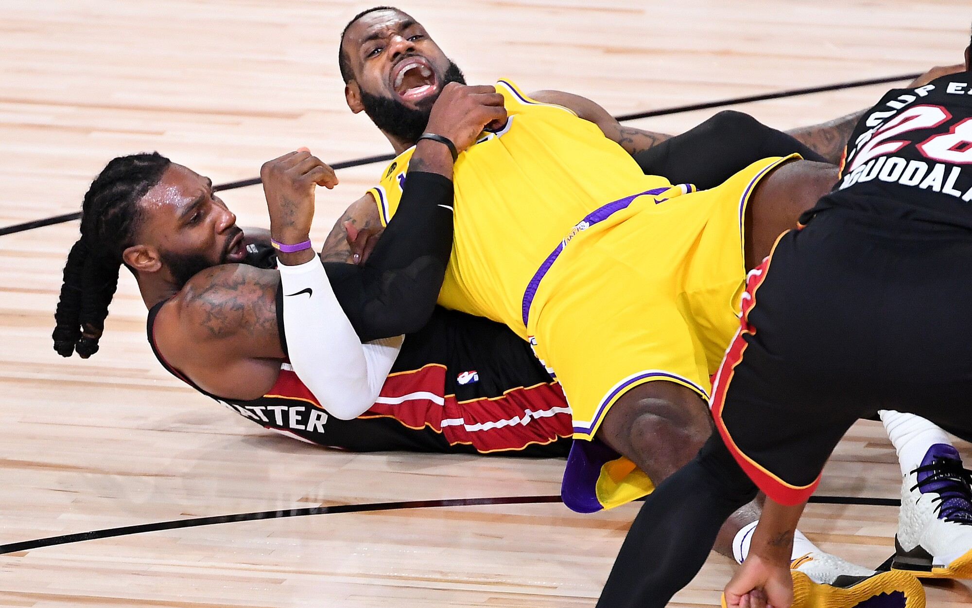 Lakers forward LeBron James falls to the court in a tangle with Heat forward Jae Crowder during Game 1.