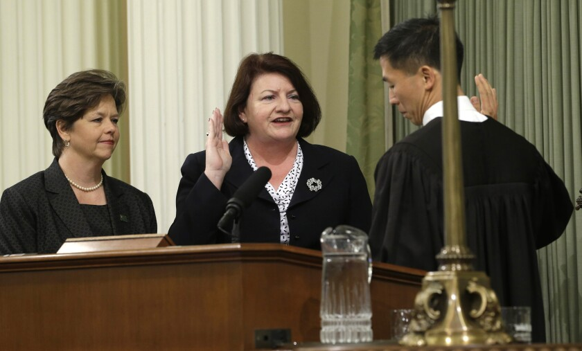 Assemblywoman Toni Atkins (D-San Diego), center, is sworn in as Assembly speaker by California Supreme Court Associate Justice Goodwin Liu, as her spouse, Jennifer LeSar, left, watches at the Capitol on Monday.
