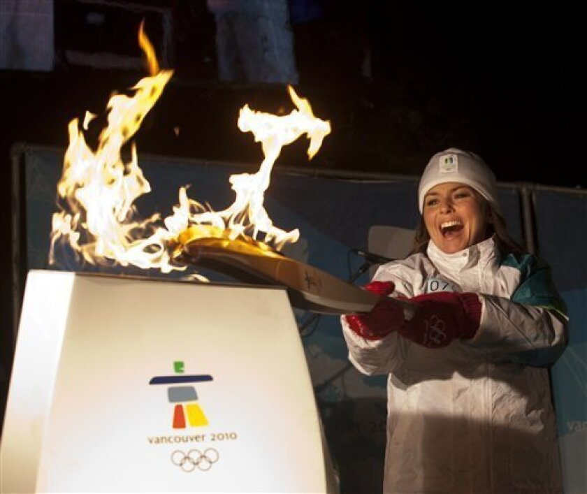 Canadian country music sensation Shania Twain lights the Olympic Cauldron with the Olympic Flame at Hollinger Park in her hometown of Timmins, Ontario on Friday, Jan. 1, 2010. The Olympic flame is passing through more than 1,000 communities on a 106-day journey before arriving in time for the Vancouver Games on Feb. 12. (AP Photo/The Canadian Press, Pawel Dwulit)