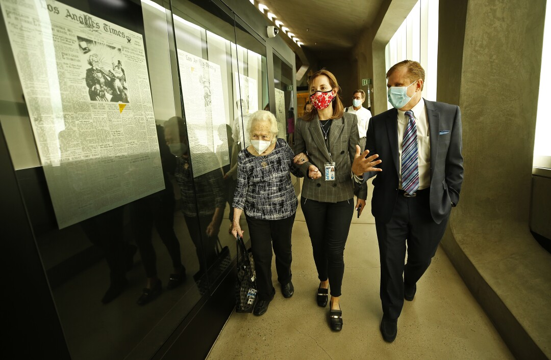 Three people walk down a hallway whose walls are lined with framed newspaper pages