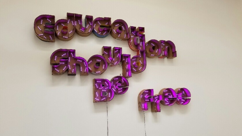 """Andrea Bowers' sign, """"Education Should Be Free,"""" is made from electric lights in cut-up cardboard shipping boxes."""