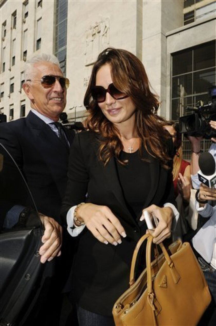 """Nicole Minetti, a Lombardy regional official who was formerly Italian Prime Minister Silvio Berlusconi's dental hygienist, leaves a Milan court, Italy, Monday, Oct.3, 2011. Minetti, according to prosecutors' documents, recruited """"a significant number of young women, who prostituted themselves with Silvio Berlusconi."""" Minetti, who is also under investigation, denies the accusations. Berlusconi is on trial from April 6, 2011 in Milan on charges of paying for sex with Karima el Mahroub, nicknamed Ruby, a 17-year-old Moroccan gilr. Berlusconi has been in court for a number of business-related charges, but this is the first time the 75-year-old billionaire businessman is being tried for personal conduct. (AP Photo/Luca Bruno)"""