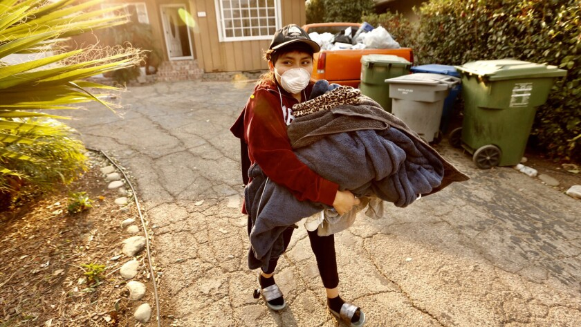 Maria Narvaez carries clothing as she leaves her home on Almon Drive near Hillcrest Drive in Thousand Oaks on Friday morning.