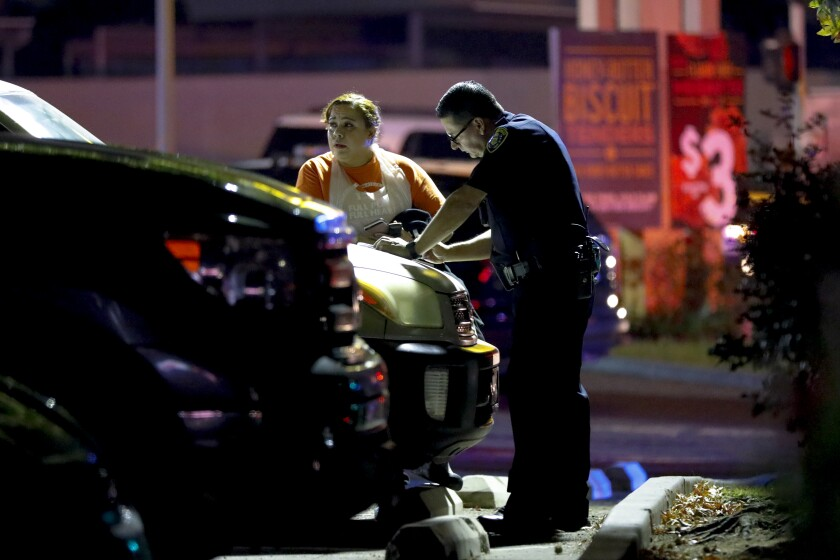 A San Diego police officer questions a witness after the shooting at a Church's Chicken restaurant in Otay Mesa.