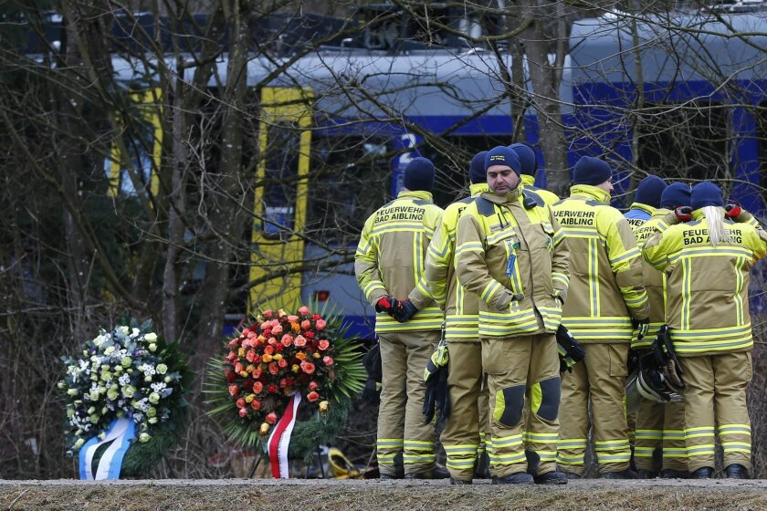 Rescue workers stand besides wreaths in front of two trains that collided head-on near Bad Aibling, Germany,  Wednesday, Feb. 10, 2016. At least ten people have been killed and dozens were injured in the accident. (AP Photo/Matthias Schrader)