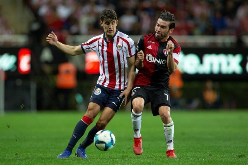 El jugador de Chivas, Josecarlos Van Rankin (i) disputa el balón con Juan Vigón (d) de Atlas. EFE/Archivo