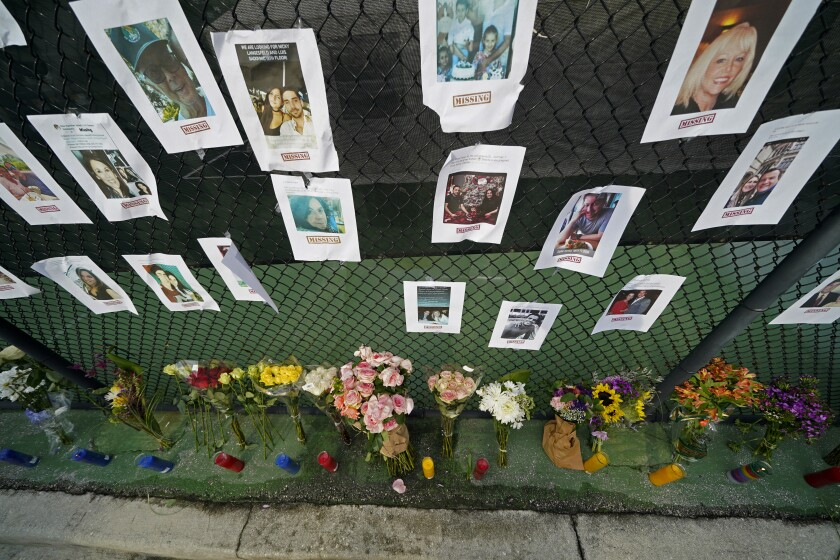 Photos of the missing hang from a chain-link fence above flowers and candles