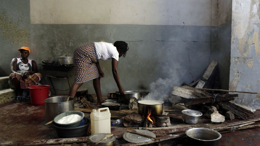 A woman cooks on the floor at a displacement centre in Beira, Mozambique, Friday, March 22, 2019. A