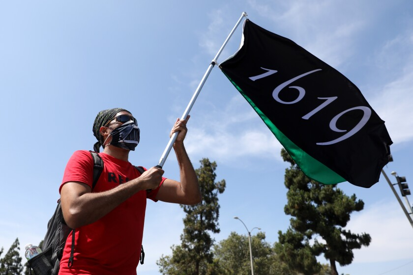 A marcher carries a flag with the year 1619 in the 2020 Juneteenth march in Los Angeles.
