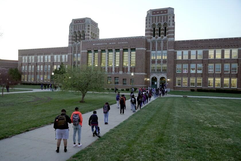 En esta imagen del miércoles 31 de marzo de 2021, estudiantes esperan para ingresar a la Escuela Secundaria del Condado de Wyandotte, en Kansas City, Kansas, para el primer día de clases presenciales. (AP Foto/Charlie Riedel, Archivo)