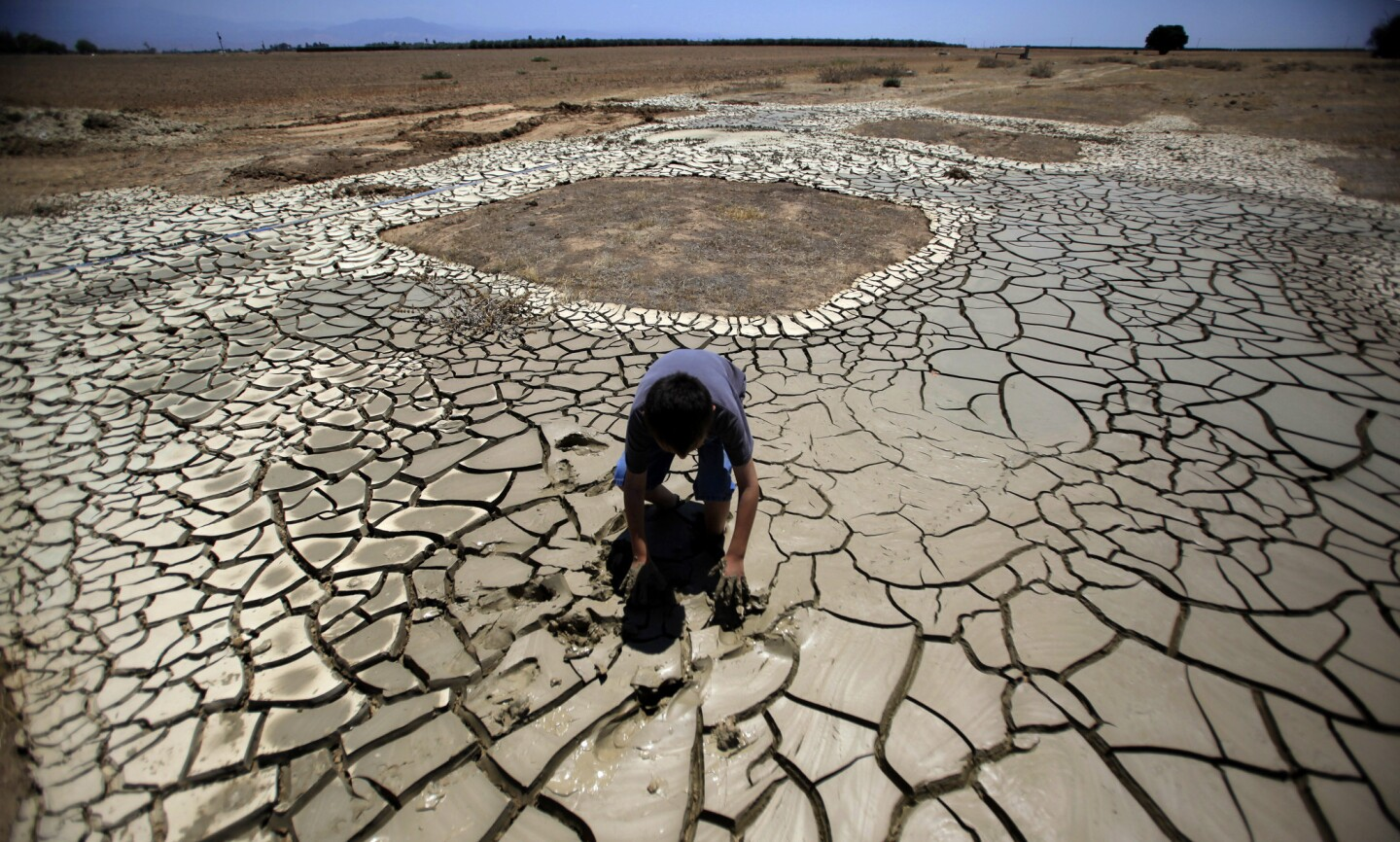 Brandon Arthur, 10, crawls out of the gooey muddy tailings left by his father Steve Arthur's water well drill site in Terra Bella.