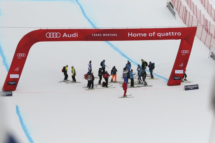 Race officers inspect the finish area of an alpine ski, women's World Cup downhill, in Crans Montana, Switzerland, Sunday, Feb. 14, 2016. (AP Photo/Gabriele Facchiotti)