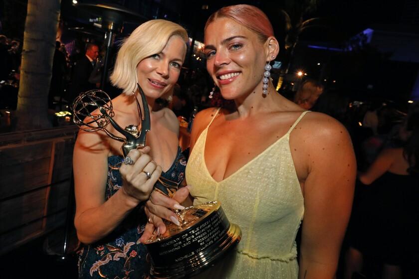 Michelle Williams clutches an Emmy beside bestie Busy Phillips.