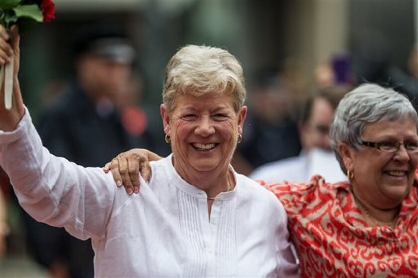 Delaware State Sen. Karen Peterson, left, and her spouse Vikki Bandy wave to supporters in Wilmington, Del., Monday, July 1, 2013. The two are the first couple to be legally wed under the state's new gay marriage law. (AP Photo/The Wilmington News-Journal,Robert Craig) NO SALES