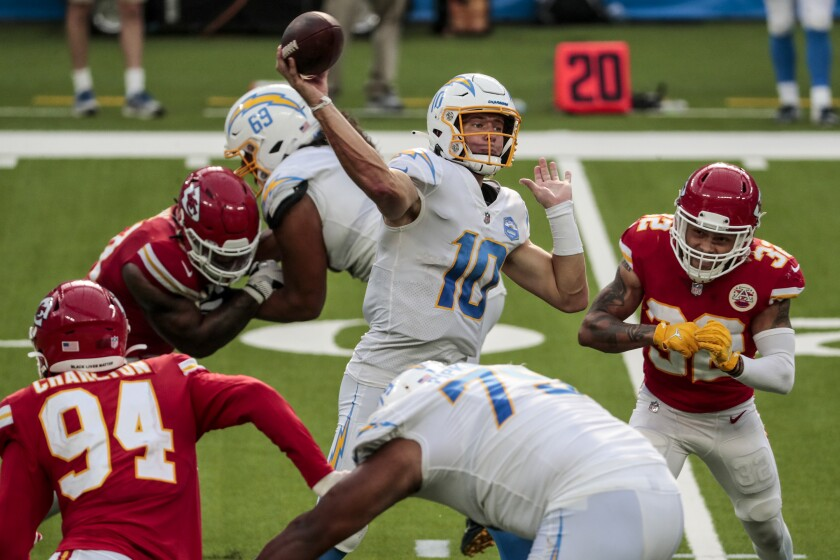 Chargers quarterback Justin Herbert throws despite pressure from the Chiefs' defense.