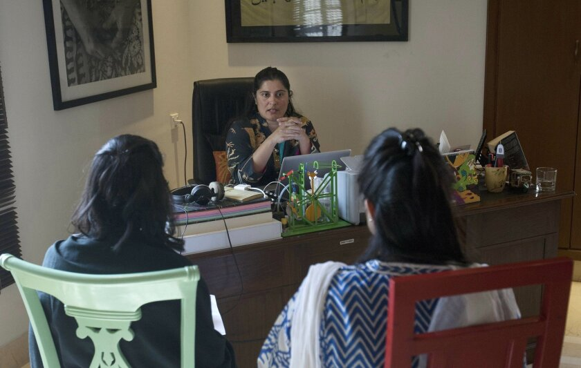 In this Tuesday, Feb. 2, 2016 photo, Pakistan's Oscar winning filmmaker, Sharmeen Obaid-Chinoy discusses with colleagues at her office in Karachi, Pakistan. Obaid-Chinoy is nominated for a second Oscar for her moving story of a teenage girl shot and dumped into a river because she married a man of