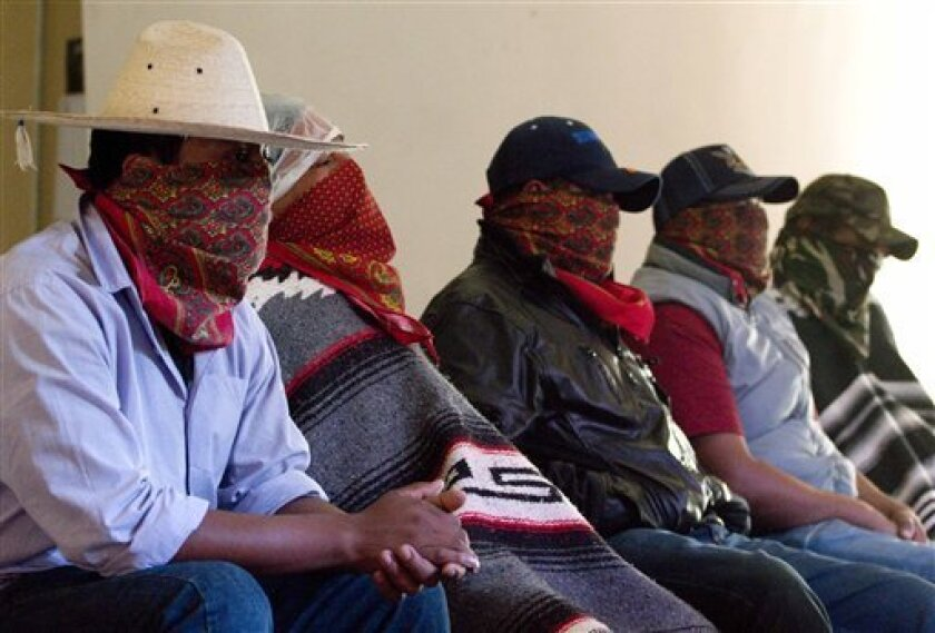 FILE - In this July 29, 2013 file photo, masked members of the Purepecha Indian community guard unit, from the town of Los Reyes in Michoacan, Mexico, attend a press conference in Mexico City. A group of farmers and businessmen from the western Mexico state of Michoacan demanded Wednesday Aug. 14, 2013 that the government stop sending thousands of federal police to fight a local drug cartel. (AP Photo/Gabriela Sanchez, File)