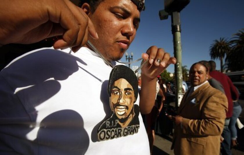 Nigel Bryson, 23, who had been riding the train with Oscar Grant the night he was killed at the BART Fruitvale Station in Oakland on News Years eve in 2009 wears a large pendant painted with Grant's face.