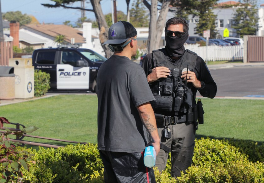 Carlsbad police Officer Chris Collier, a member of the Homeless Outreach Team, speaks with Ronnie Quick, a homeless man.