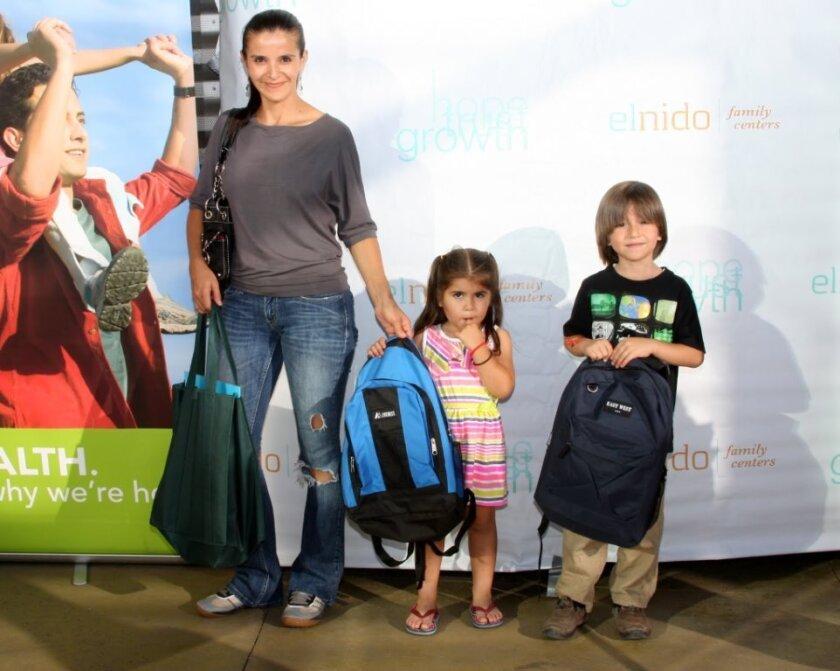 Una familia recibe sus mochilas.