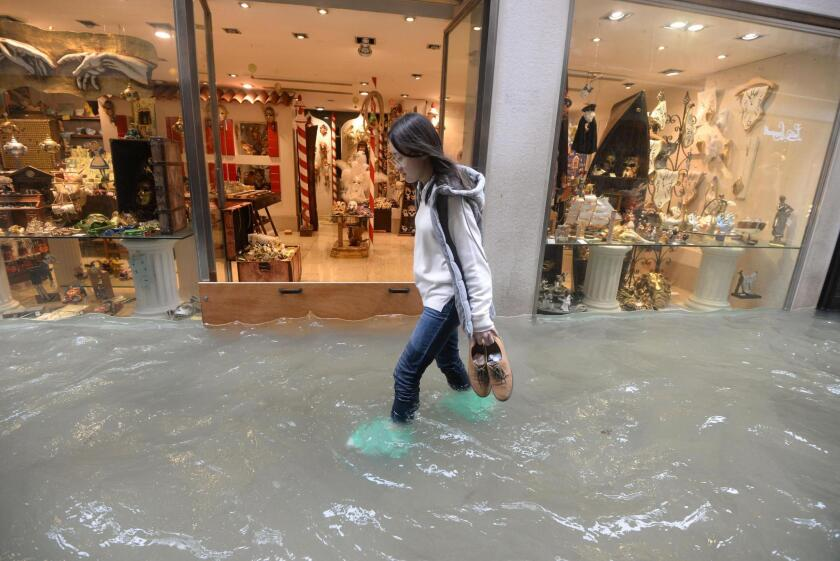 A woman walks in a flooded street of Venice, Italy on Monday.