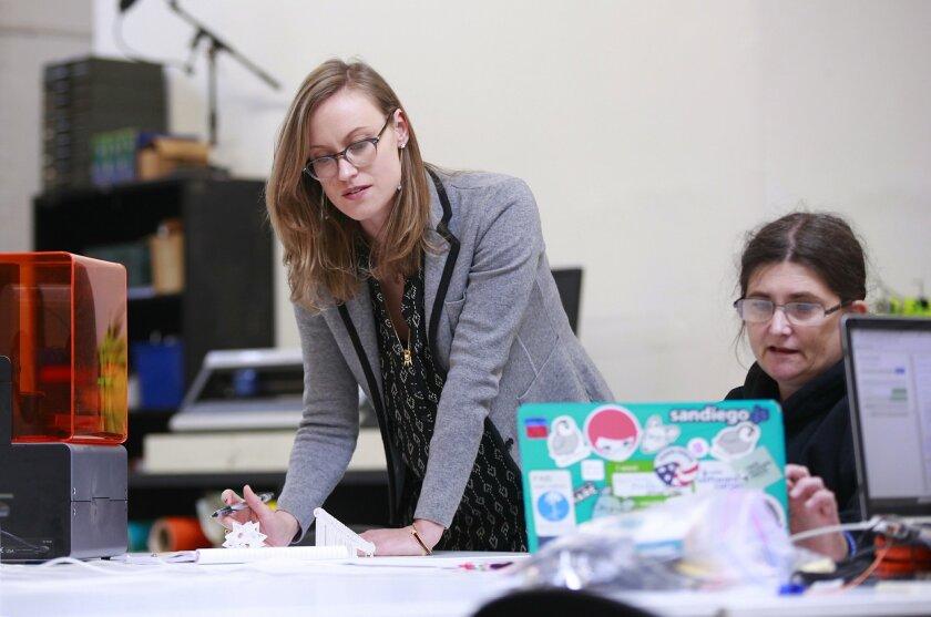 Katie Rast, standing, advises Fab Lab client Carol Willing.